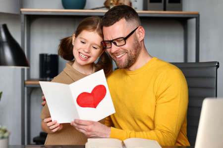 Small child daughter giving handmade postcard daddy on Father day while he working on laptop, young happy man dad getting congratulations from kid at home. Family holidays concept