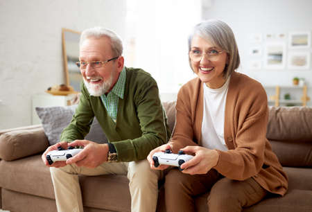 Excited concentrated senior couple husband and wife playing video console games together while sitting on couch in living room at home, laughing and having fun. Leisure time and people concept Фото со стока