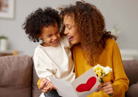 With love. Cute excited little boy son giving his mom handmade greeting postcard and flower bouquet, happy mother embracing with with child while sitting on sofa at home. Mothers day celebration concept