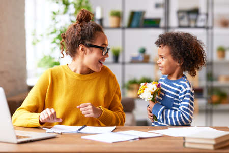 Happy Mothers day. Young mixed race woman mom getting congratulations from excited cute little son at home, child giving mother flower bouquet while she working on laptop. Family holidays concept
