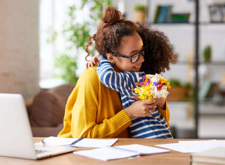 Little child son congratulating mom with Mothers day or birthday, giving her fresh flower bouquet. Happy mixed race woman mother embracing with child while working at home. Family holidays concept Фото со стока