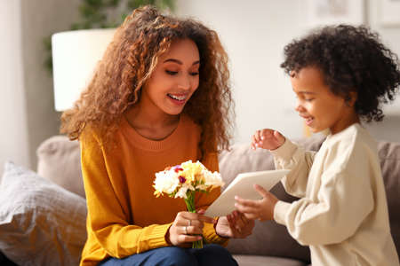 With love. Cute excited little boy son giving his mom handmade greeting postcard with red heart, happy mother embracing with with child while sitting on sofa at home. Mothers day celebration concept