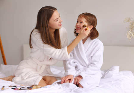 Cheerful young woman in bathrobe smiling and applying powder on cheeks of delighted girl while resting on bed during skin care routine Фото со стока