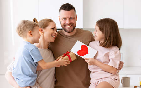 Young happy beautiful family with children celebrating Fathers Day or Birthday together at home. Smiling mother and two cute kids congratulating daddy with holiday and giving him presents in kitchen Фото со стока