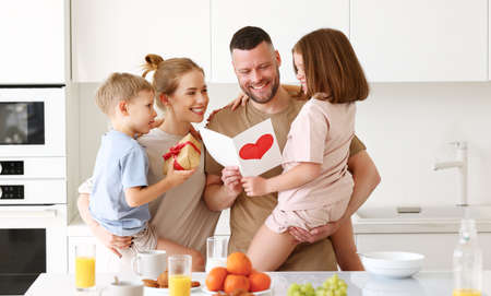 Young happy beautiful family mom, dad and children standing in kitchen and hugging while celebrating Fathers Day together at home. Cute little son and daughter giving daddy greeting postcard and gift box