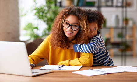 Working with kids. Young focused woman mother wearing eyeglasses using laptop and thinking about work task while small boy son gently hugs her. Childcare concept