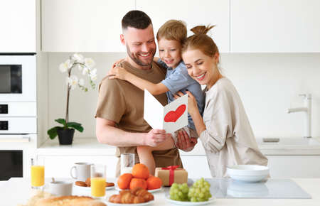 Young happy beautiful family mom, dad and child standing in kitchen and hugging while celebrating Fathers Day together at home. Cute little boy son giving daddy greeting postcard with red heart Фото со стока