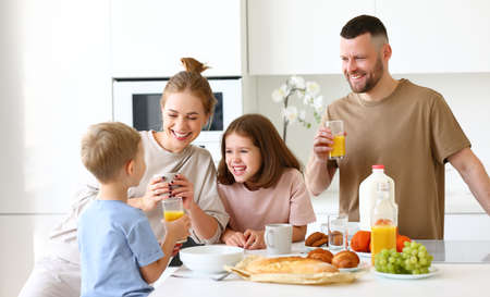 Family morning at home. Happy father, mother and two kids brother and sister enjoying time together while having healthy breakfast, drinking tea, orange juice and eating cookies in kitchen Фото со стока