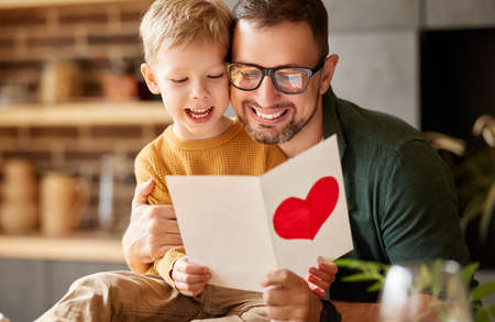 Portrait of happy family father with excited child son hugging smiling while celebrating Fathers day together at home. Little boy congratulating giving dad homemade greeting postcard