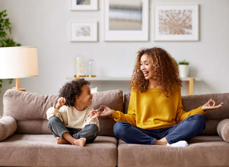 Yoga with kids. Young afro american family mother and little son meditating while sitting in lotus pose on sofa in living room, smiling and enjoying leisure time together at home
