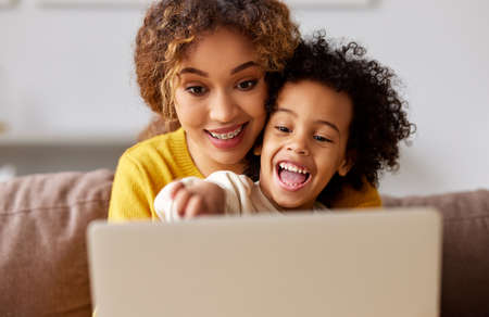 Excited little boy son watching video or cartoons on laptop with young smiling mother, pointing with finger at computer screen and keeping mouth opened, a mom and kid spending leisure time at home