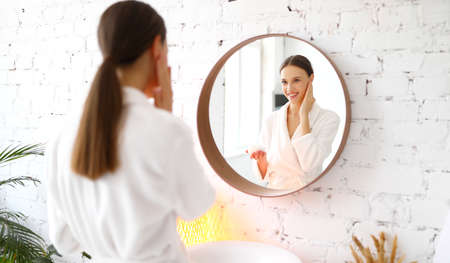 Happy young female in bathrobe applying cosmetic cream on face and enjoying softness of skin during spa beauty session at home
