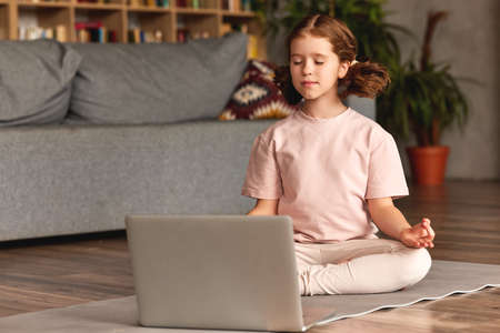 Yoga for kids. Calm little girl in casual wear with closed eyes sitting in lotus pose in front of laptop in living room at home while having yoga class online