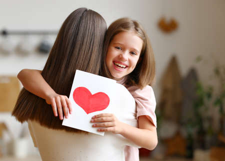 Excited girl holding greeting card with heart and hugging woman on blurred background of room during Mother Day celebration Фото со стока