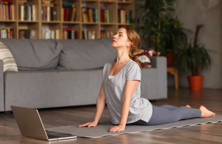 Young peaceful woman with closed eyes wearing sportswear doing yoga or stretching exercises on floor in living room at home, practicing asana in front of laptop. Active lifestyle during covid19