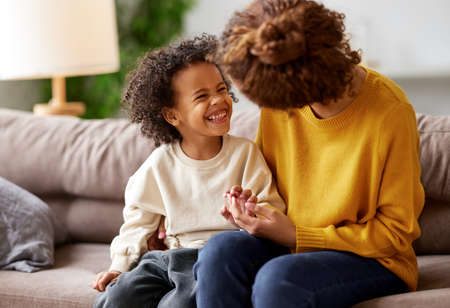I love you, mom. Happy african american child son holding mothers hand, looking at her and smiling while sitting together on sofa in living room. Young family mom and kid enjoying time together at home
