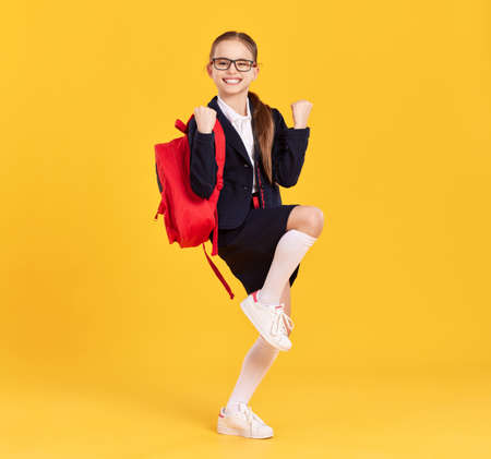 Happy smart schoolgirl in uniform and glasses with backpack keeping fists up and doing yes gesture while celebrating achievement against yellow background