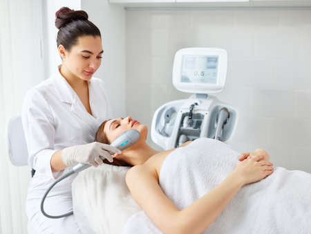 Young relaxed woman receiving professional facial treatment and SMAS lifting with laser machine from cosmetologist in modern beauty salon Фото со стока