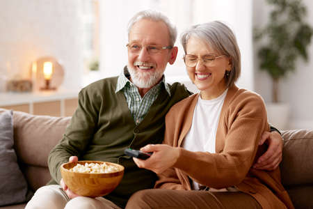 Beautiful happy senior couple husband and wife eating popcorn and watching TV while relaxing on sofa in the living room. Laughing mature family cuddling enjoying weekend together. Leisure activities