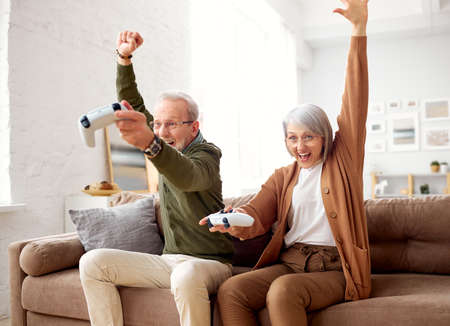 Celebrating victory. Excited senior couple, retired man and woman with wireless contollers sitting on couch in living room at home, laughing and having fun while playing video console games together