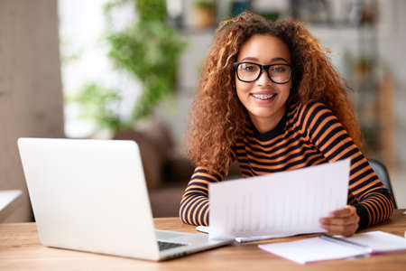 Portrait of cheerful young afro american woman smiling at camera while working with documents at her home office, working on laptop remotely. Happy mixed race female student studying online from home Фото со стока
