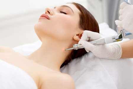 Crop unrecognizable cosmetologist using modern laser device while removing mole on neck of female patient in professional clinic