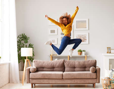 Enjoying freedom. Full length of overjoyed young afro american woman in casual wear jumping and dancing in living room, happy mixed race female teenager spending carefree time having fun alone at home