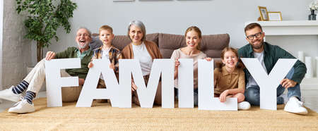 Housing and mortgage concept. Big happy family of six people grandparents, mother and father with little kids holding word FAMILY smiling at camera while sitting on floor near sofa in the living room in new home