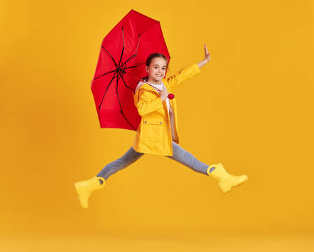 Full body side view of excited little girl in yellow raincoat and boots with red umbrella having fun and jumping above ground against yellow background