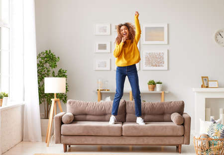 Pretending to be famous singer. Overjoyed afro american teenage girl in casual wear singing and dancing on sofa in modern living room at home. Young happy female enjoying carefree and leisure weekend