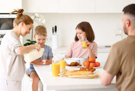 Young positive mom pouring fresh milk from bottle in glass while having healthy breakfast with two cute kids, daughter and son. Happy family of four spending time in kitchen while eating morning meal