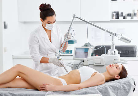 Relaxed young female client receiving professional body contouring treatment with laser tool during appointment in modern beauty clinic Фото со стока