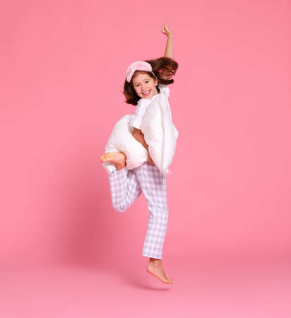 Full length happy girl in pajama raising arms with soft pillow and smiling while jumping against pink backdrop in morning