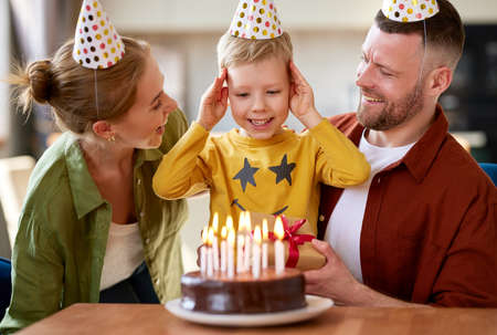 Happy little boy son going to blow candles on cake while celebrating Birthday with young loving parents, excited kid raising arms and smiling while receiving congratulations and presents from family Фото со стока