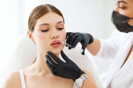 Young female patient getting injection to lips from professional cosmetologist in mask and gloves in beauty procedure in modern clinic Фото со стока