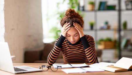 Stressed young afro american woman holding head in hands and feeling demotivated while sitting at her home office and working remotely on laptop. Depressed female student tired of onling learning Фото со стока