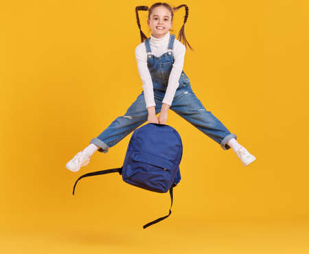 Full body of happy energetic primary schoolgirl with pigtails wearing denim jumpsuit holding backpack in hands and jumping high against yellow background