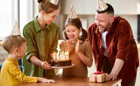 Excited little girl going to blow candles on chocolate cake while and making wish while celebrating her Birthday with happy family at home, positive parents in party hats congratulating daughter