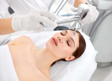 Professional cosmetologist using laser equipment for skin care treatment on face of female client in modern beauty clinic