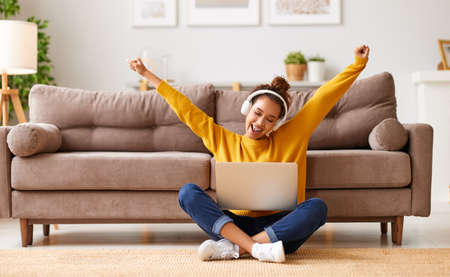 Full length of carefree afro american teenage girl wearing headphones listening music while studying online on laptop, happy female student celebrating success sitting on floor in living room at home Фото со стока