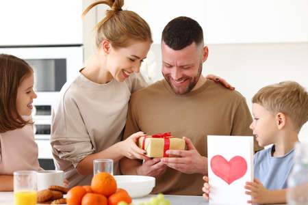 Surpise for daddy. Cute smiling children siblings giving father wrapped gift box and postcard. Young mom congratulating husband with kids while having breakfast in kitchen at home. Family holiday concept