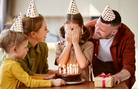 Cute little girl wearing party hat covering eyes with hands and making wish while celebrating Birthday with family at home, going to blow candles on chocolate cake, parents giving gift box to daughter
