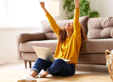 Full length of excited happy afro american woman female student with laptop celebrating success in study, raising arms up and laughing while sitting on floor in living room and studying online at home Фото со стока