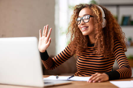 Cheerful young african american woman in headphones greeting colleague via webcam on laptop while working remotely from home, happy female student having video call with teacher while studying online