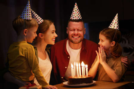 Time to make a wish. Young happy beautiful family with children wearing party hats congratulating father with Birthday at home. Excited dad with covered eyes going to blow candles on chocolate cake