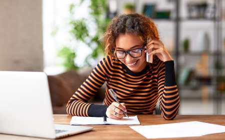 Cheerful young african american woman talking with client on mobile phone, smiling and making some notes while working remotely on laptop from home, happy female office worker making business call Фото со стока
