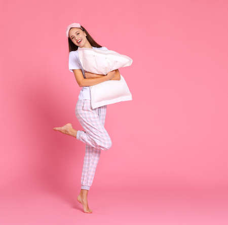 Full body delighted woman in sleepwear smiling and embracing soft pillow while standing with raised leg against pink backdrop in morning Фото со стока