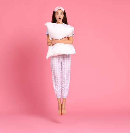 Full body delighted amazed woman in sleepwear smiling and embracing soft pillow while jumping against pink backdrop in morning