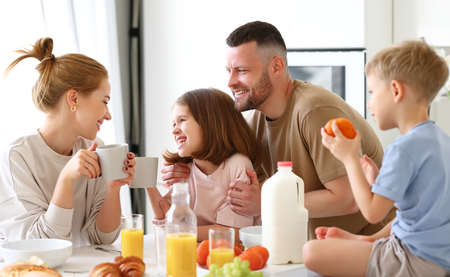 Young happy beautiful family having breakfast together at home. Father, mother and two cute little kids eating healthy food in morning, talking and smiling while standing in modern kitchen