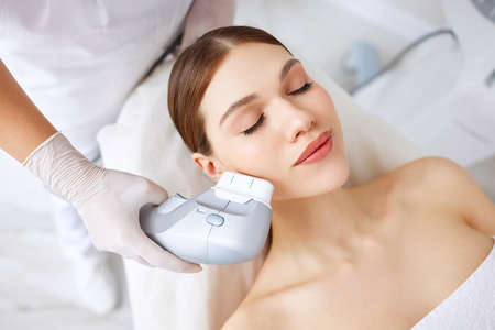 From above of relaxed young female client getting SMAS ultrasound face lifting massage with professional equipment in beauty center
